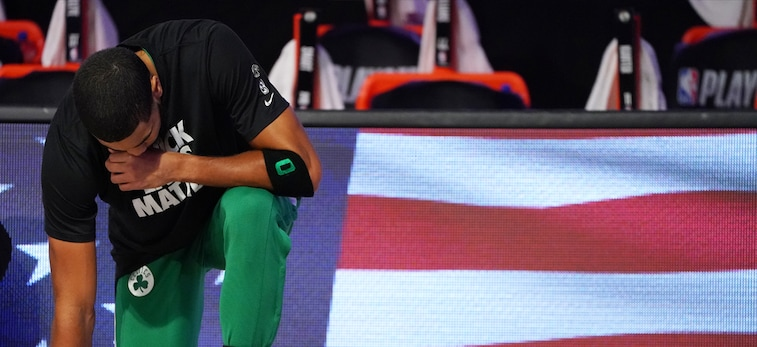 Jayson Tatum takes a knee during the national anthem