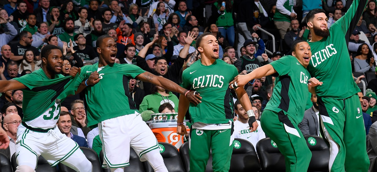 The Celtics on the sideline celebrate a big play on the court