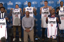Players holding up jerseys after free agent press conference