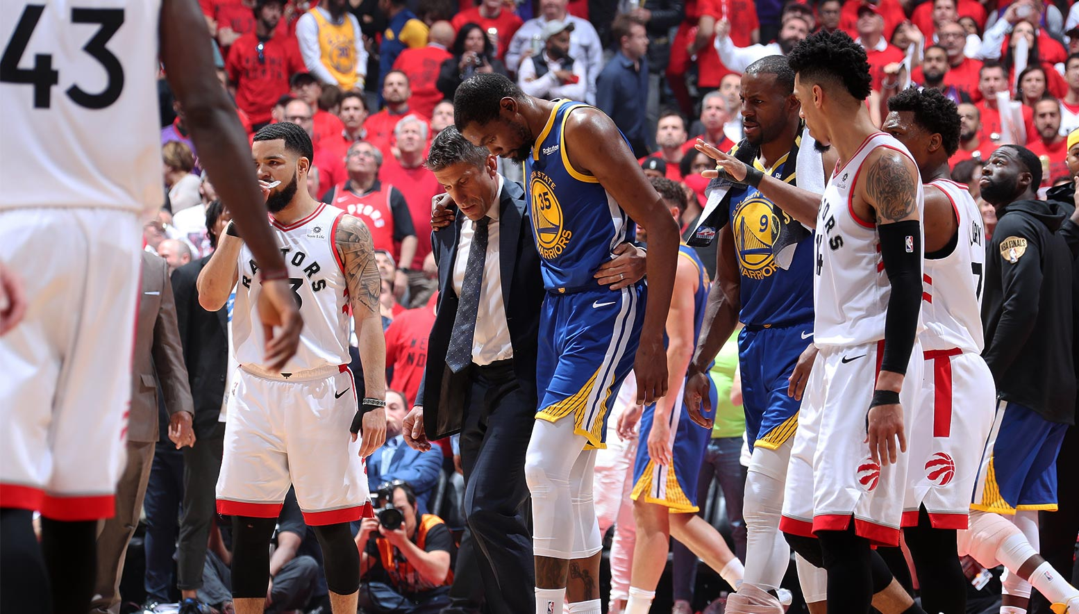 Kevin Durant is assisted off court after injuring his leg