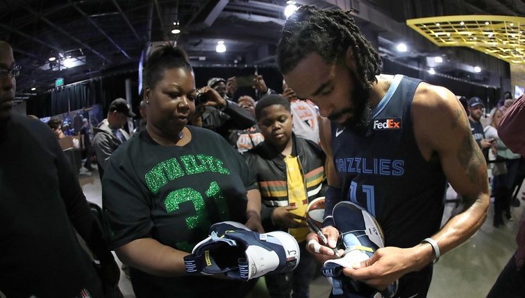 Mike Conley #11 of the Memphis Grizzlies meets the family of Kameron Johnson prior to a game against the Cleveland Cavaliers on December 26, 2018 at FedExForum in Memphis, Tennessee.