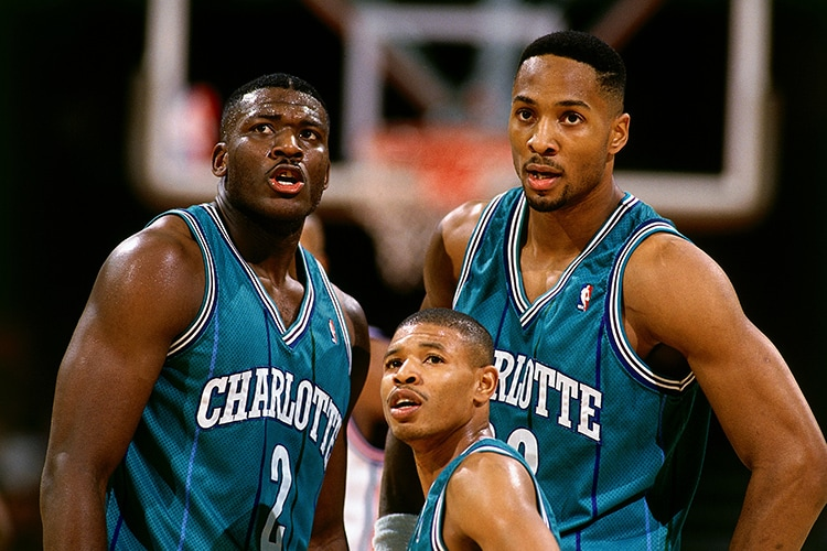 CHARLOTTE, NC - 1993: (L-R) Larry Johnson #2, Muggsy Bogues #1 and Alonzo Mourning #33 of the Charlotte Hornets take a break during an NBA game circa 1993 at The Charlotte Coliseum in Charlotte, North Carolina.(NBAE Getty Images)