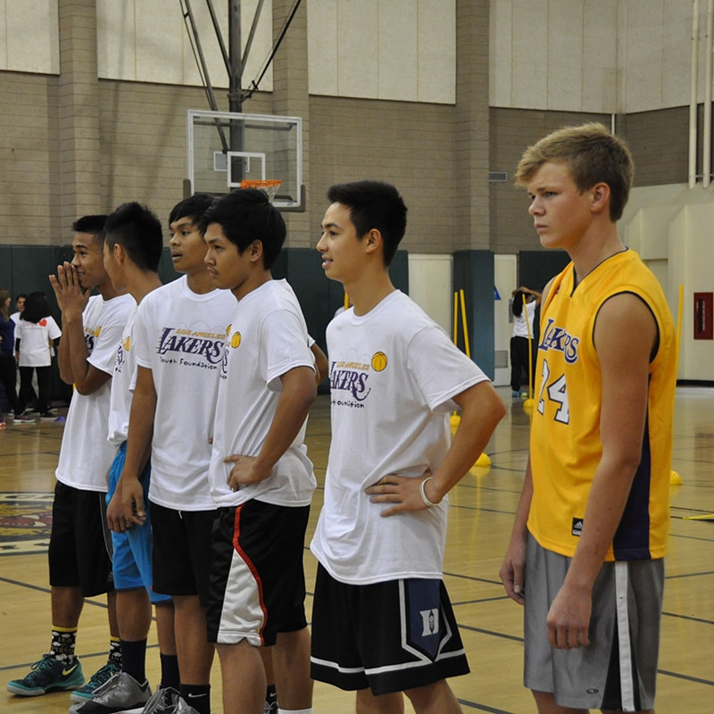 Kids look on and listen to instructions and advice given to them by Lakers Legends at Youth Camps.