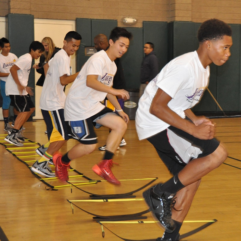 Kids run through the ladder drill, which is used to increase agility and footwork in athletes of all ages.
