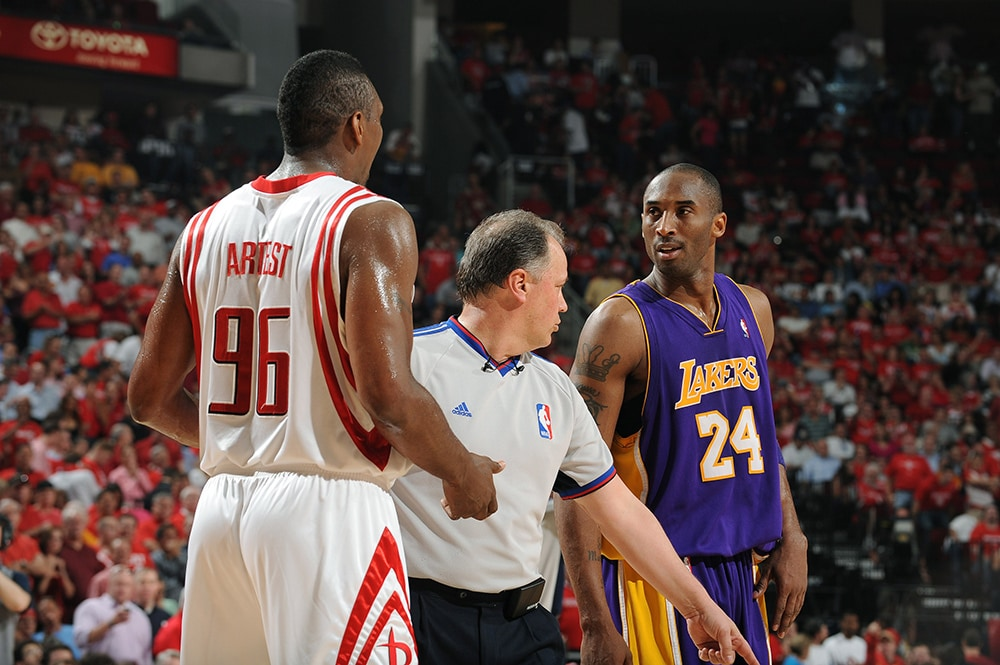 Artest and Kobe Bryant are separated by an official after a heated exchange.