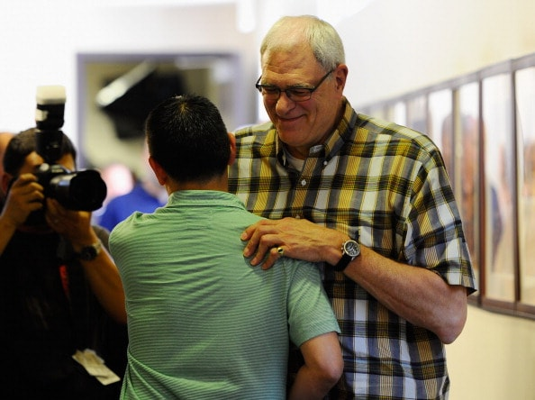 Kevin Ding and Phil Jackson embrace after final press conference
