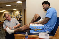 Head Athletic Trainer Jim Gillen tapes the ankle of Wilson Chandler of the Denver Nuggets prior to a game.