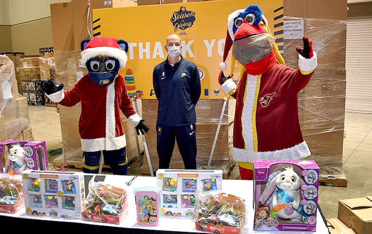Pacers coach Nate Bjorkgren with Boomer and Freddy at Holiday Toy Distribution