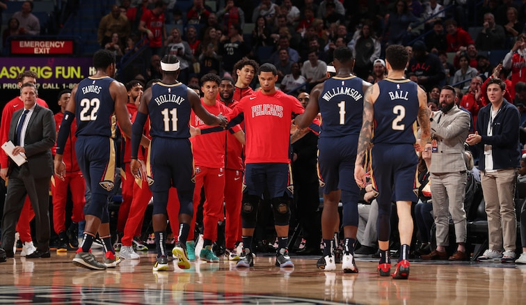 Pelicans players greet each other during a timeout at Smoothie King Center