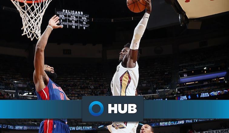 Jrue Holiday tries to dunk over Andre Drummond