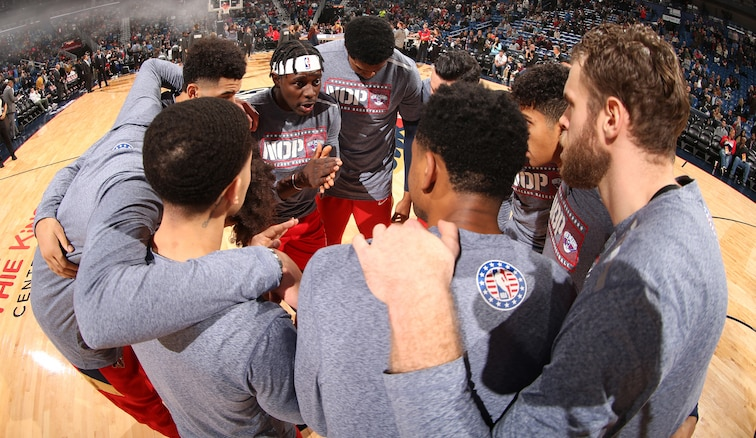 Jrue Holiday leads a full team huddle before a home game