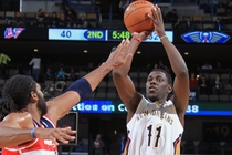 Pelicans guard Jrue Holiday fires a jumper over Washington's Nene