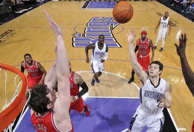 While playing for Sacramento, Jimmer Fredette lofts a shot over then-Chicago center Omer Asik