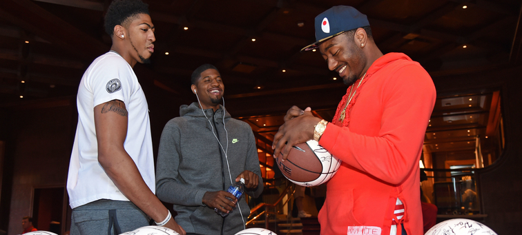 Anthony Davis jokes with Paul George (middle) and John Wall (right) as Wall signs a basketball