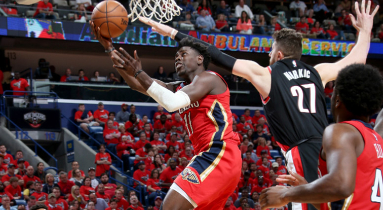 Jrue Holiday glides to the hoop past Portland's Jusuf Nurkic during the NBA playoffs