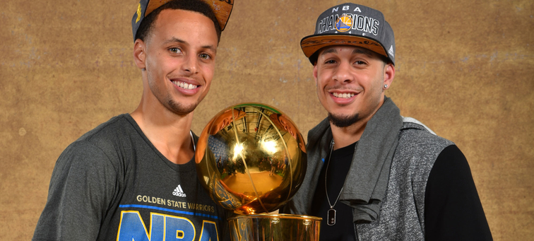 Stephen Curry (left) and brother Seth Curry pose with the NBA championship trophy