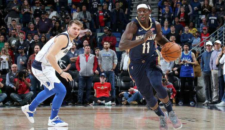 Jrue Holiday dribbles past Dallas defender Luka Doncic