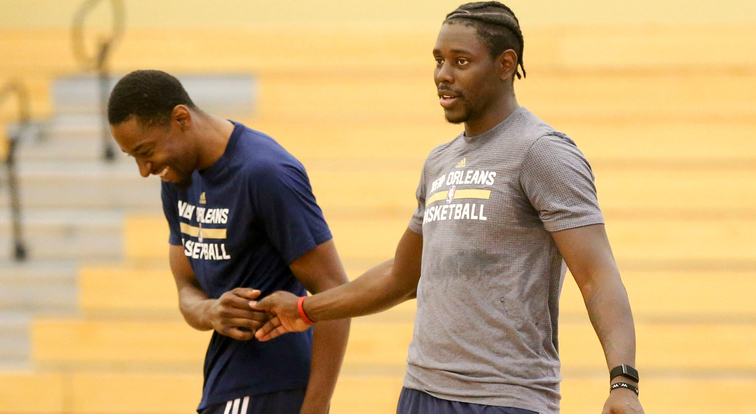 Jordan Crawford (left) shares a light moment with Jrue Holiday during Pelicans voluntary workouts