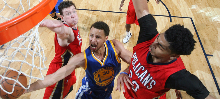 Reigning league MVP Stephen Curry splits New Orleans defenders Omer Asik and Anthony Davis