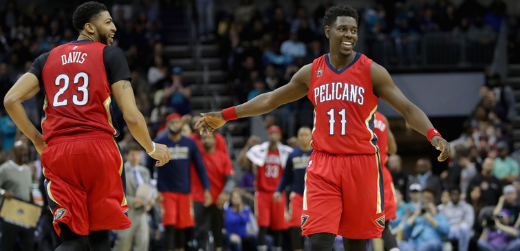 Anthony Davis (left) and Jrue Holiday low-five at Charlotte last season