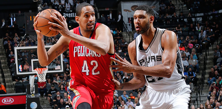 Alexis Ajinca goes to the hoop against San Antonio's Tim Duncan