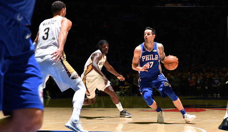 JJ Redick tries to elude New Orleans defender Jrue Holiday