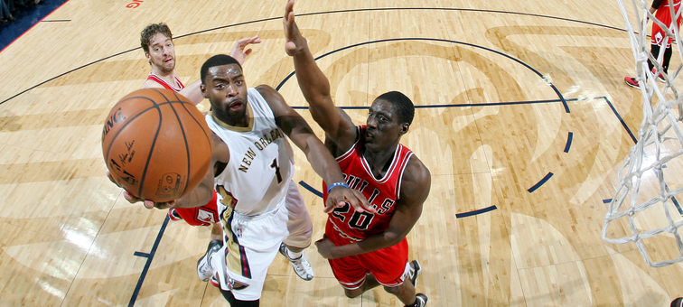 Tyreke Evans drives to the hoop past Chicago's Tony Snell and Pau Gasol for a layup attempt