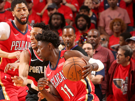 Jrue Holiday tries to drive past Evan Turner, as Anthony Davis sets a screen