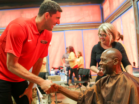 Nikola Mirotic greets a guest at the New Orleans Mission as he awaits a shave