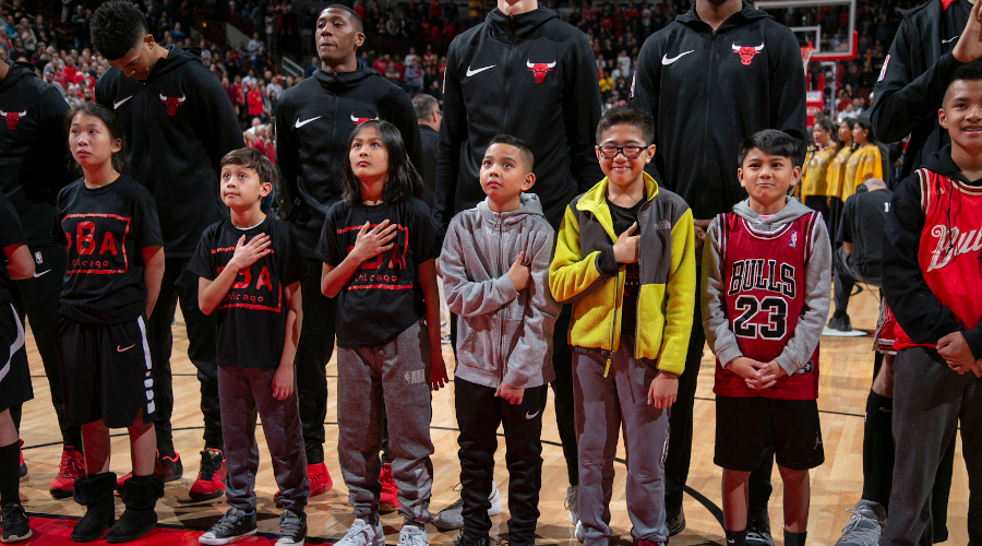 Children standing with Bulls players during the national anthem