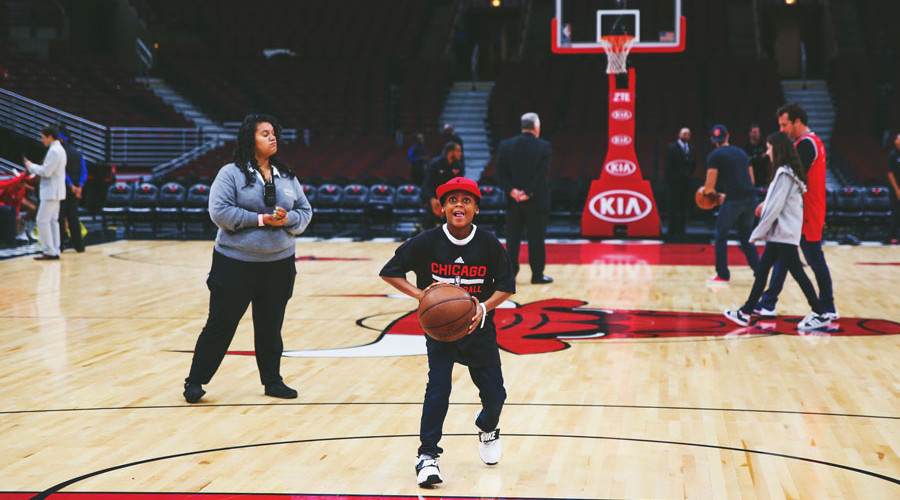 A child fan shooting a freethrow on the basketball court
