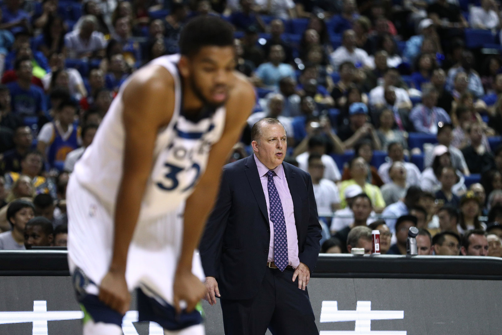 Head coach Tom Thibodeau of the Minnesota Timberwolves looks on as Karl-Anthony Towns #32 of the Minnesota Timberwolves on court during the game between the Minnesota Timberwolves and the Golden State Warriors as part of 2017 NBA Global Games China at Mercedes-Benz Arena on October 8, 2017 in Shanghai, China.