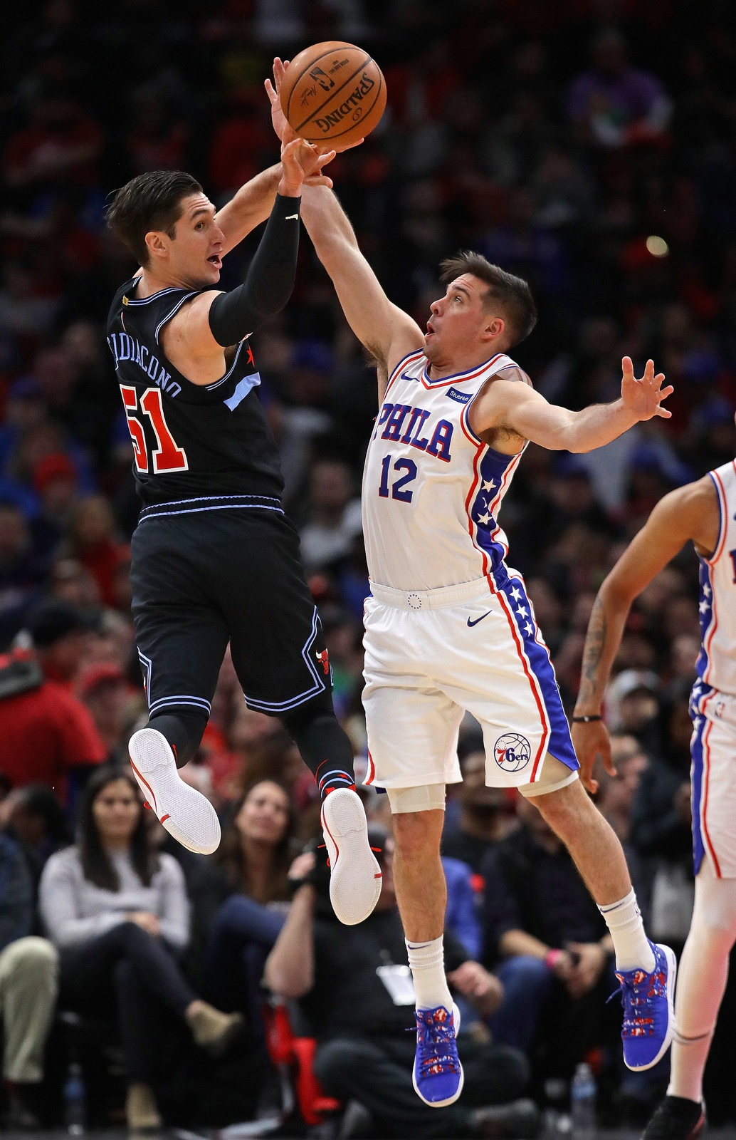 Ryan Arcidiacono #51 of the Chicago Bulls leaps to pass against T.J. McConnell #12 of the Philadelphia 76ers at the United Center on March 06, 2019 in Chicago, Illinois.