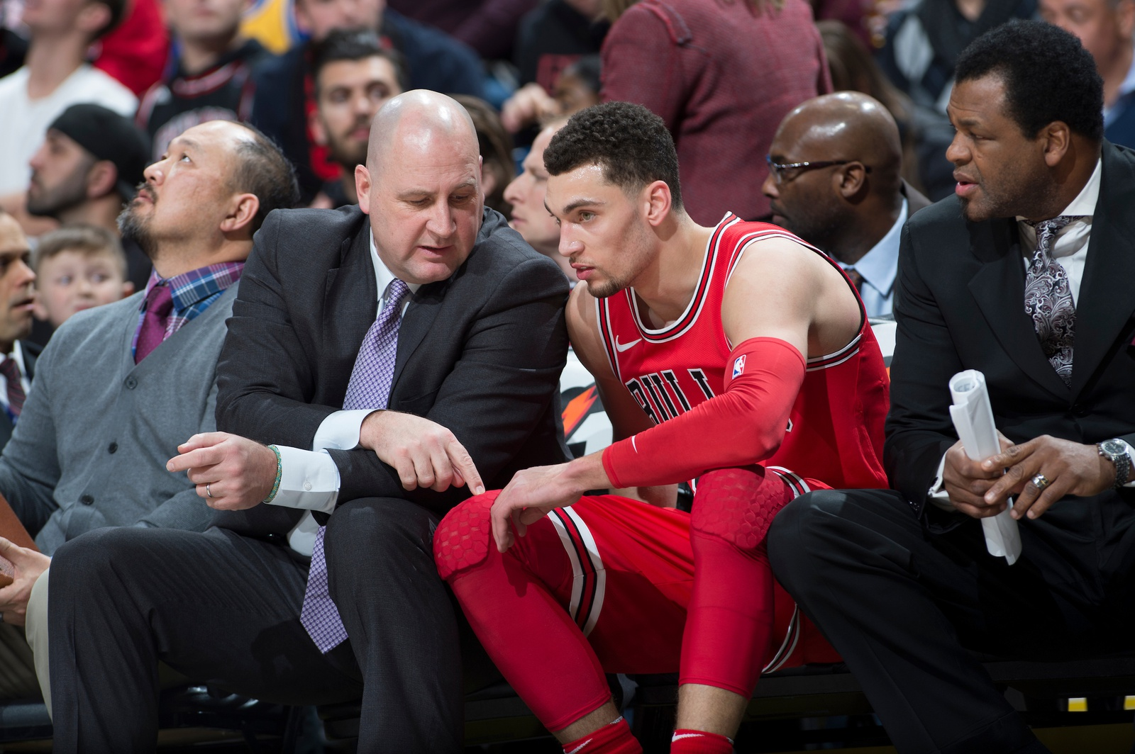 Jim Boylen talks to Zach LaVine of the Chicago Bulls while sitting on the sidelines during a game.