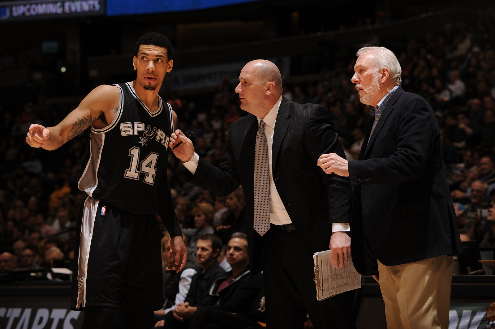 Danny Green #14, Jim Boylen and Gregg Popovich of the San Antonio Spurs speak during a game against the Denver Nuggets speaks on January 20, 2015 at the Pepsi Center in Denver, Colorado