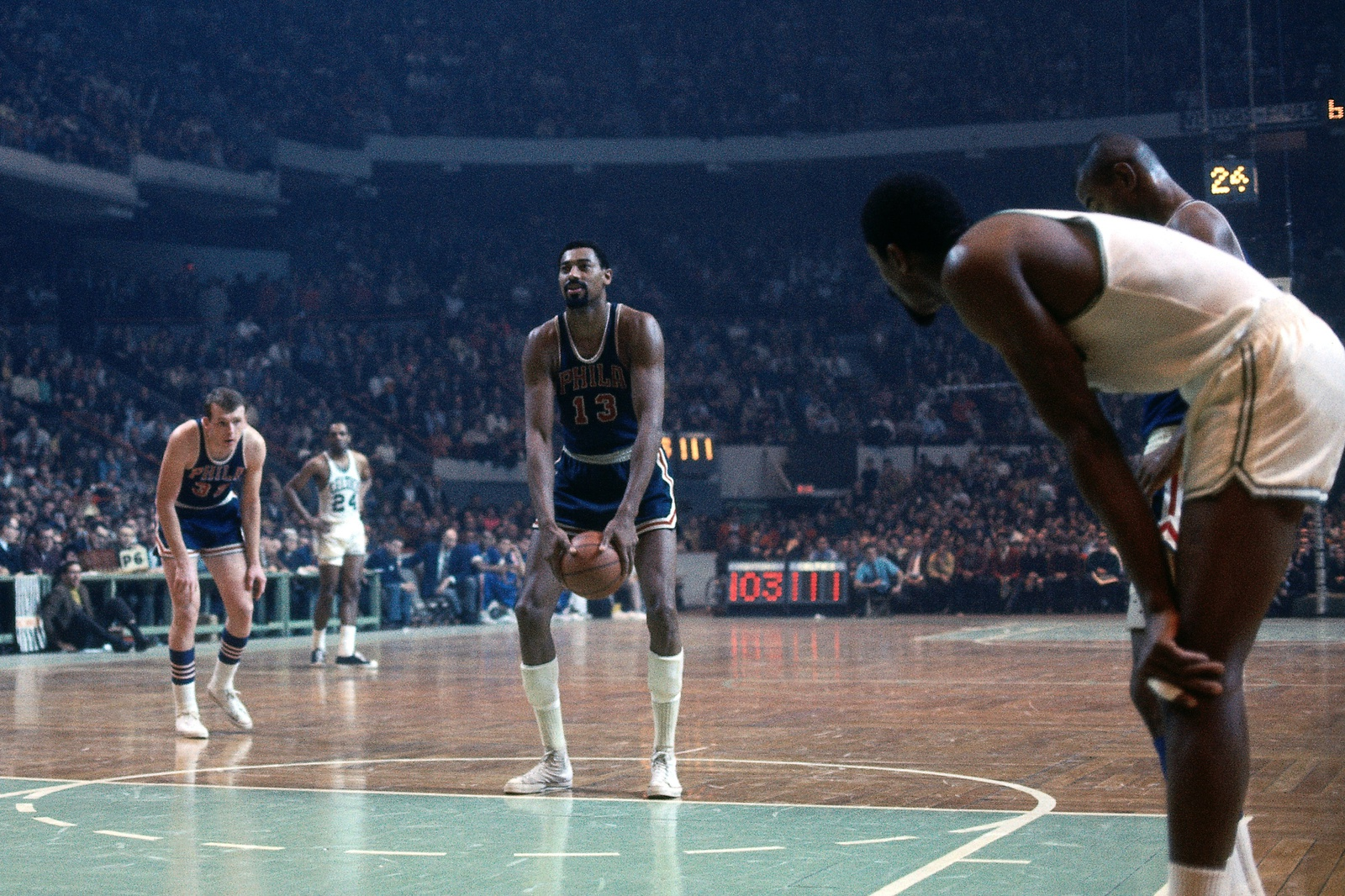 Wilt Chamberlain #13 of the Philadelphia 76ers shoots a free throw against the Boston Celtics during a game played in 1968 at the Boston Garden in Boston, Massachusetts.