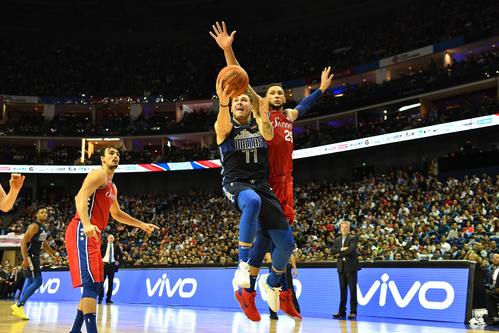 Luka Doncic #77 of the Dallas Mavericks shoots against Ben Simmons #25 of the Philadelphia 76ers as part of the 2018 China Games on October 5, 2018 at the Mercedes-Benz Arena in Shanghai, China.