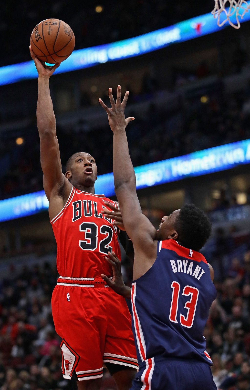 Kris Dunn #32 of the Chicago Bulls shoots over Thomas Bryant #13 of the Washington Wizards at the United Center on March 20, 2019 in Chicago, Illinois.