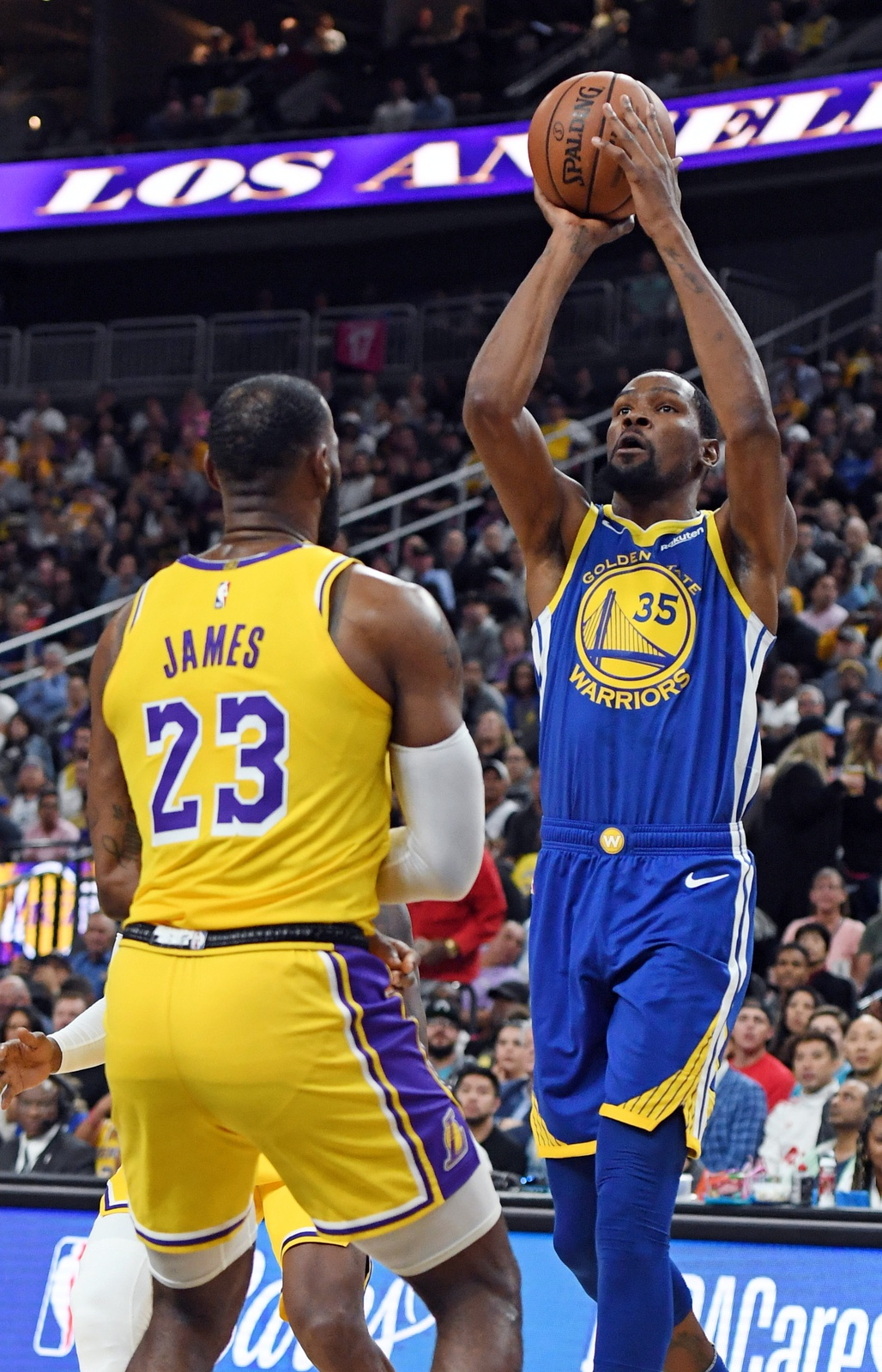Kevin Durant #35 of the Golden State Warriors shoots against LeBron James #23 of the Los Angeles Lakers during their preseason game at T-Mobile Arena on October 10, 2018 in Las Vegas, Nevada.
