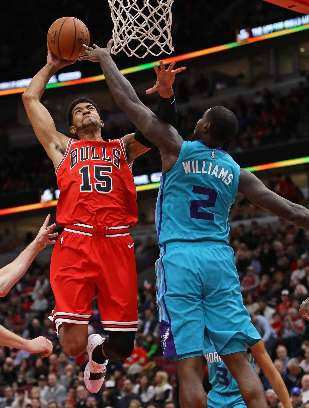 Chandler Hutchison #15 of the Chicago Bulls goes up for a dunk over Marvin Williams #2 of the Charlotte Hornets at the United Center on October 24, 2018 in Chicago, Illinois.