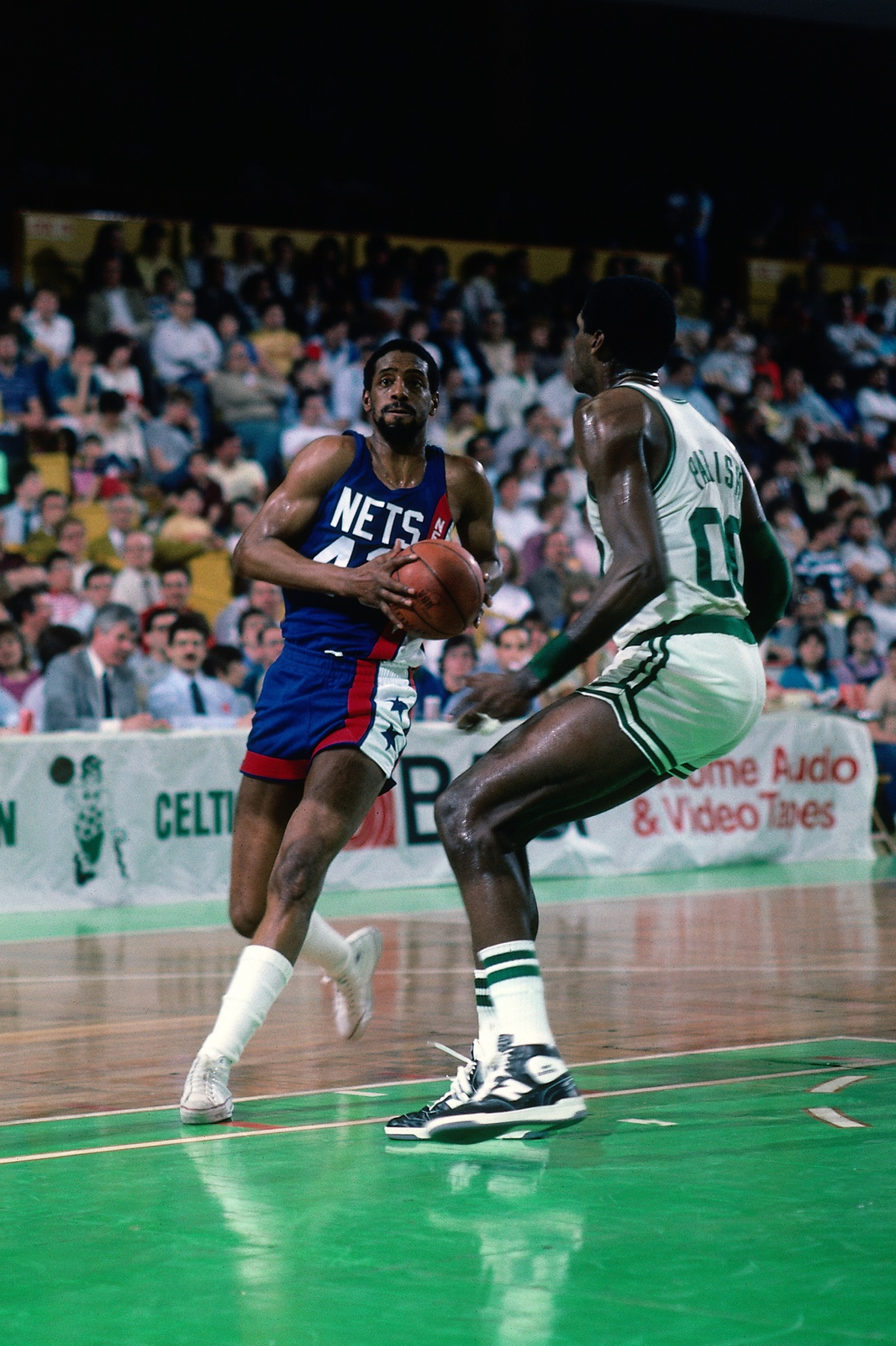 Mickey Johnson #43 of the New Jersey Nets drives against Robert Parish #00 of the Boston Celtics during a game circa 1986 at the Boston Garden in Boston, Massachusetts.