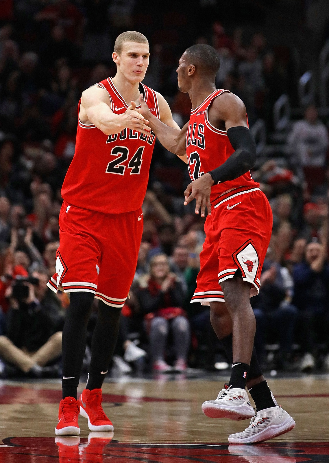 Lauri Markkanen #24 of the Chicago Bulls is congratulated by Kris Dunn #32 after hitting a three point shot against the Washington Wizards at the United Center on March 20, 2019 in Chicago, Illinois.