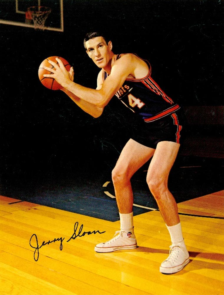 Jerry Sloan wearing a Baltimore Bullets jersey and posing with a basketball.