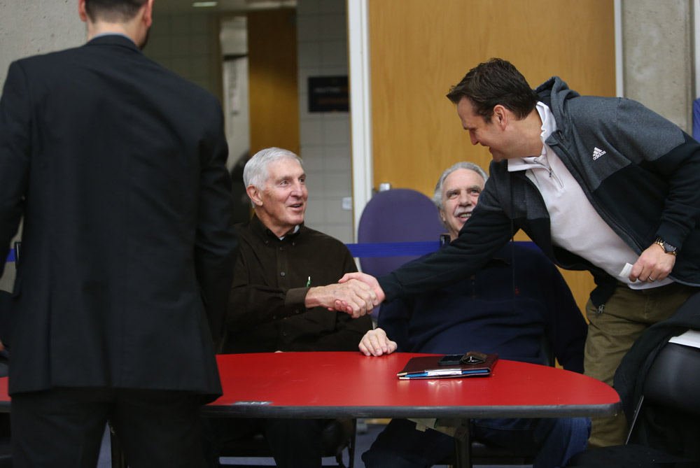 Jerry Sloan shaking hands with another person.