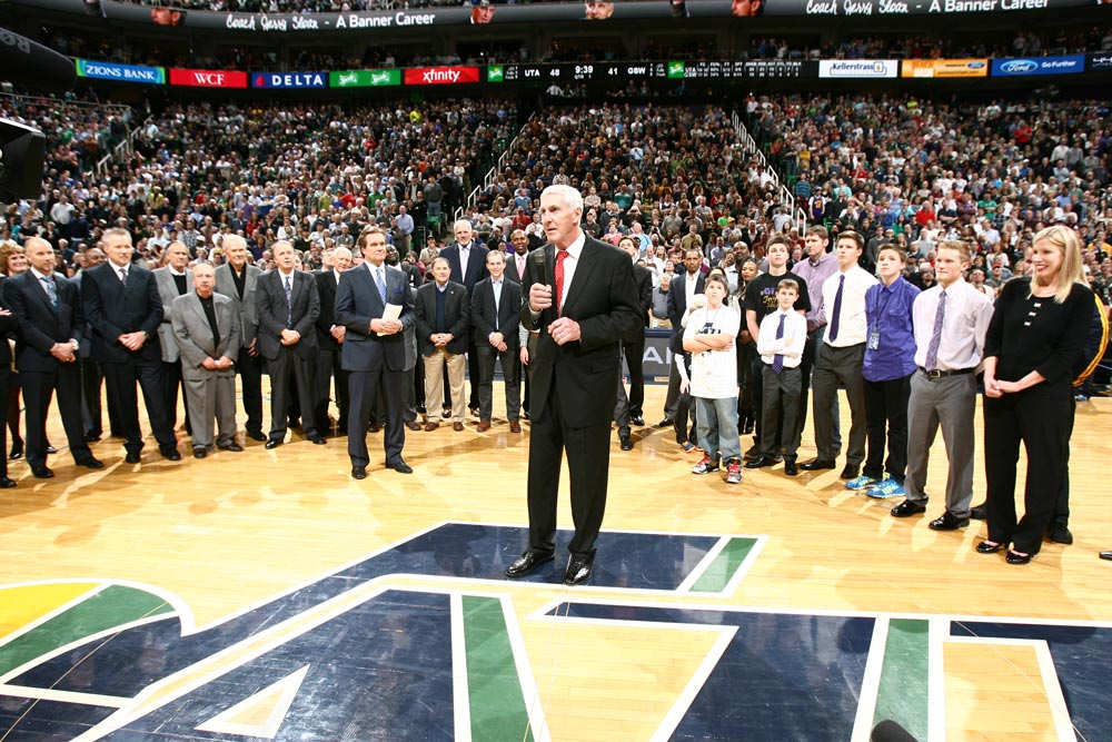 Jerry Sloan giving a speech in front of a crowded arena.