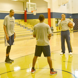 Pelicans assistant coach Randy Ayers works with center Alexis Ajinca