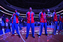 Michael Carter-Williams stands during the singing of the National Anthem during a home game in 2013-14