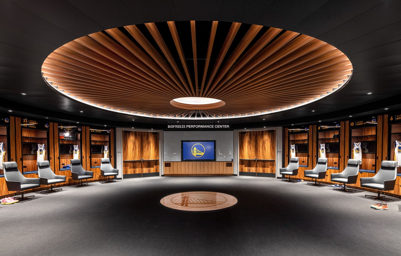The locker room, which includes a ceiling that resembles the roof of Oracle Arena, has the team's 2015 NBA Championship court inlaid on the floor in the center of the room.