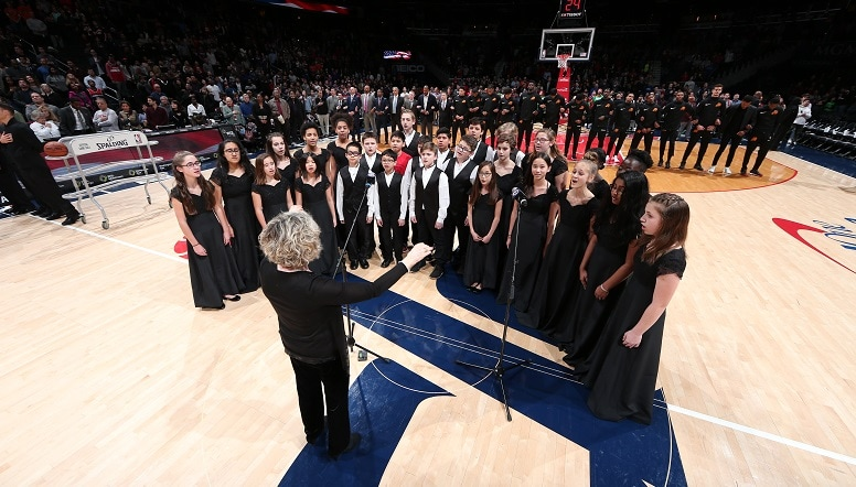 A chorus performing the National Anthem mid-court at Capital One Arena
