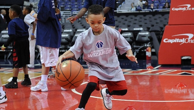 A young boy dribbles a basketball at Capital One Arena